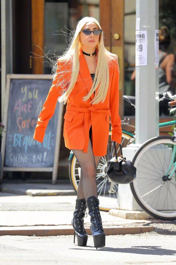 Lady Gaga重返狂放路線,以橘色外套、網襪、GZD黑色皮革綁帶靴穿出她的鮮...