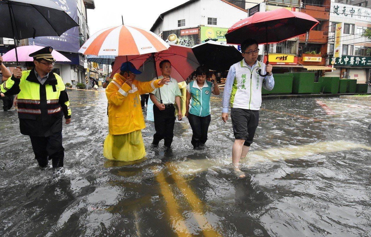 彰化縣長魏明谷(中)今天下午3點多到員林市西區了解當地街道淹水情形。記者何烱榮/...