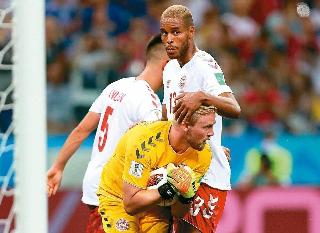 丹麥門將舒米切爾(前)緊抱著球,隊友捷安森摸著他的頭表示讚許。 (歐新社)