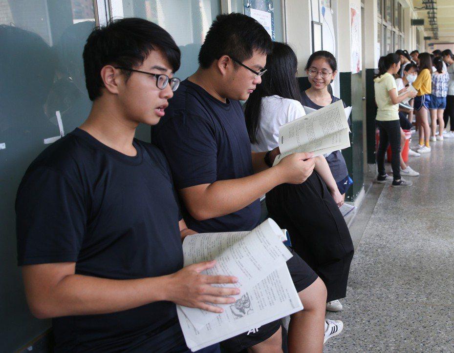 大學指考3日進行最後一天考試,同學們在教室外溫習功課等待開放進入考場。 中央社