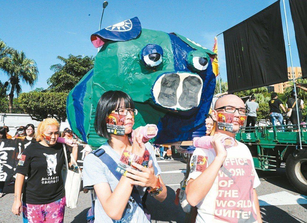2015年11月凱道秋鬥遊行,民眾行進時扛著「藍綠豬」,最後在蔡英文競選總部前以...