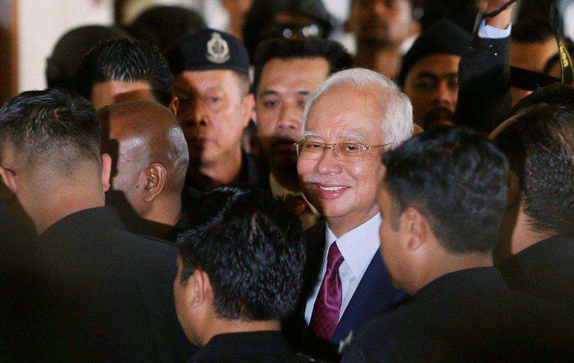 被捕的馬來西亞前首相納吉,在4日上午打著紅領帶微笑出庭。 圖/路透社