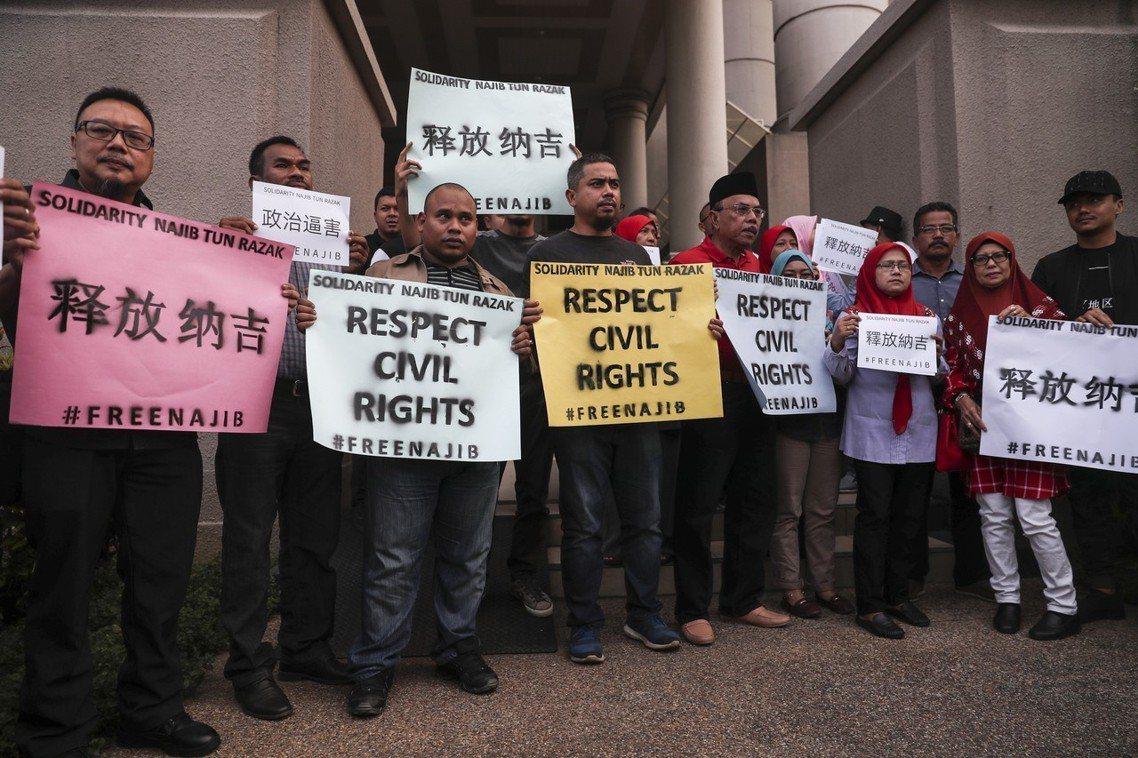 納吉的支持者,在法庭外高呼「釋放納吉」口號,抗議馬哈迪司法迫害。 圖/歐新社