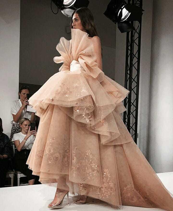 Alexis Mabille的玫瑰色禮服,有著浪漫刺繡裙襬與蝴蝶結縐褶的前襟。圖...