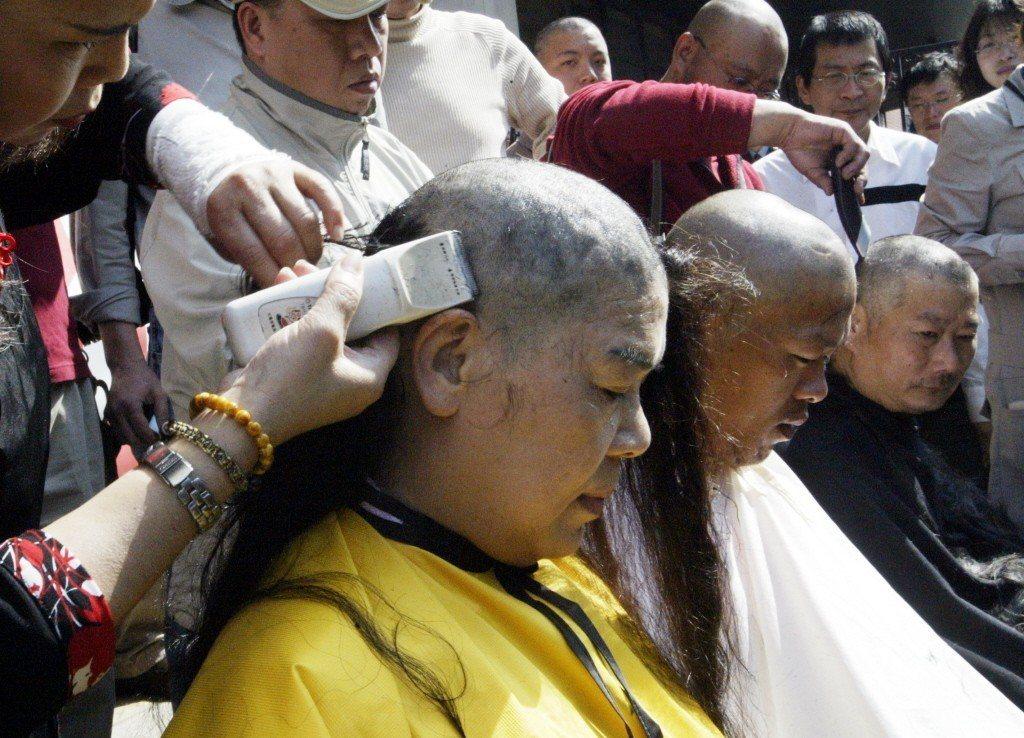 2008年3月,拒領公投票聯盟包括鄭女士(左)等十餘位男女志工,在立法院外以「剃...