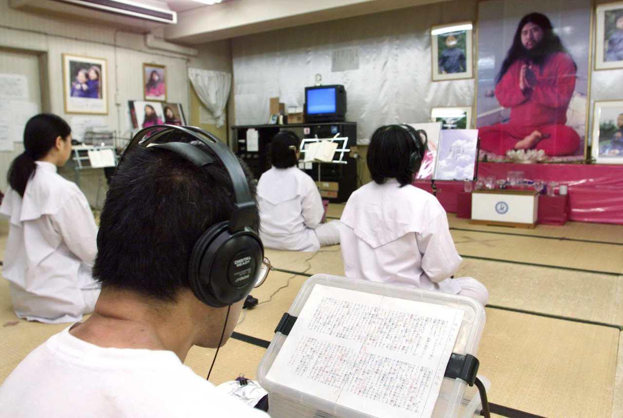 圖為1999年7月19日,日本奧姆真理教的信徒在東京聚會所對著教主麻原彰晃的肖像...