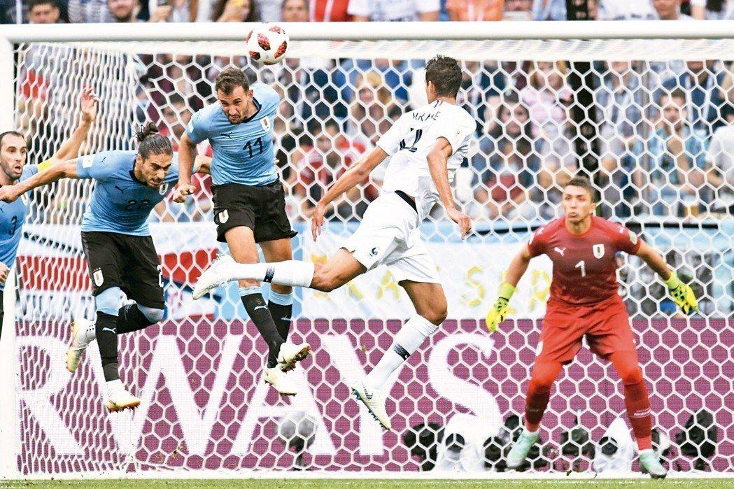 法國瓦拉內(右二)躍起頭錘,球飛過烏拉圭的防守球員,為球隊頂進第一球。 (法新社...