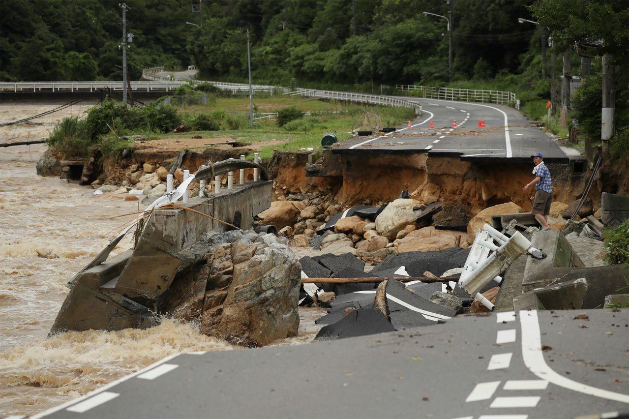 七日拍攝的照片顯示,日本廣島縣東廣島市一條馬路被暴洪沖斷。法新社
