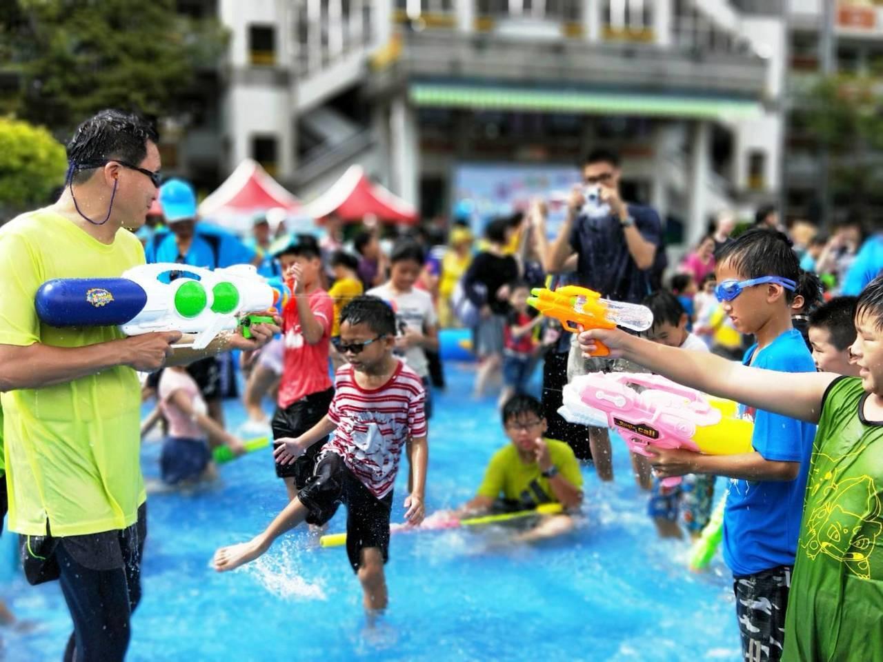 員林市長張錦昆不計形象,拿起水槍跟一群小朋友在戲水池大玩水槍戰,成為眾「槍」之的...