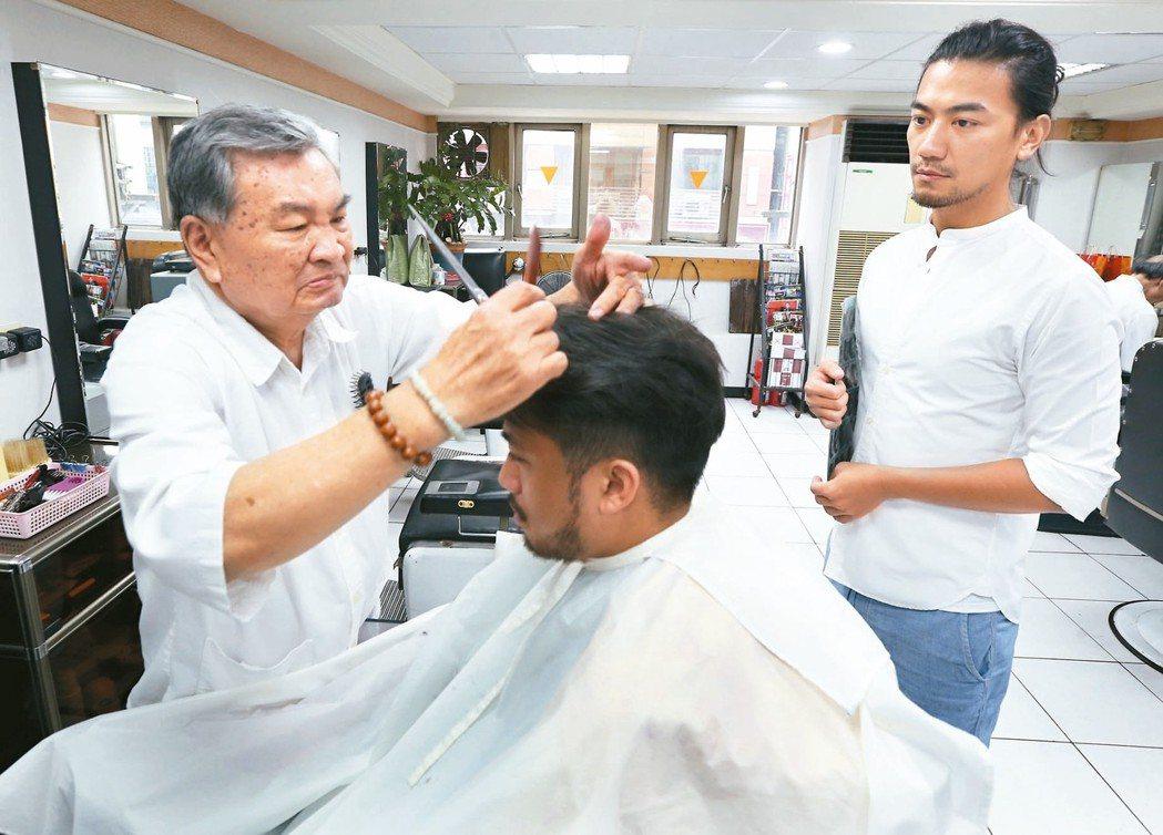 傳統理髮廳邱師傅(左)為年輕髮型設計師張華(右)傳授修剪復古髮型技術。 記者侯永...