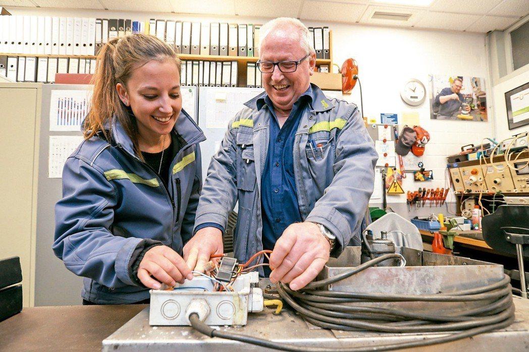 德國漢諾威交通運輸公司,61歲電工榭爾法根(右)與28歲帕魯荷一同完成工作。 特...