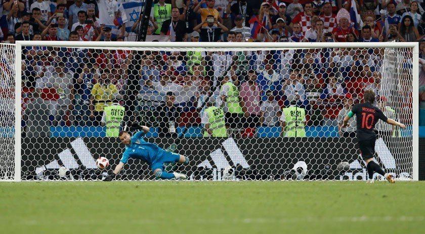 克羅埃西亞的莫德里奇(右)在PK賽中射中左邊門柱,但球又反彈進入網內,讓俄羅斯只...