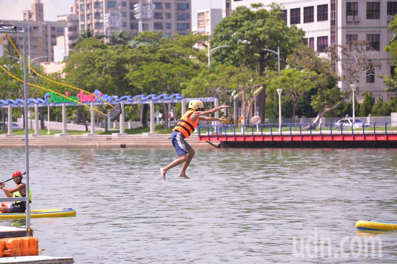 今天高雄艷陽高照,下午愛河水上活動推出盪鞦韆跳愛河,出現不少跳水的年輕人。記者謝...