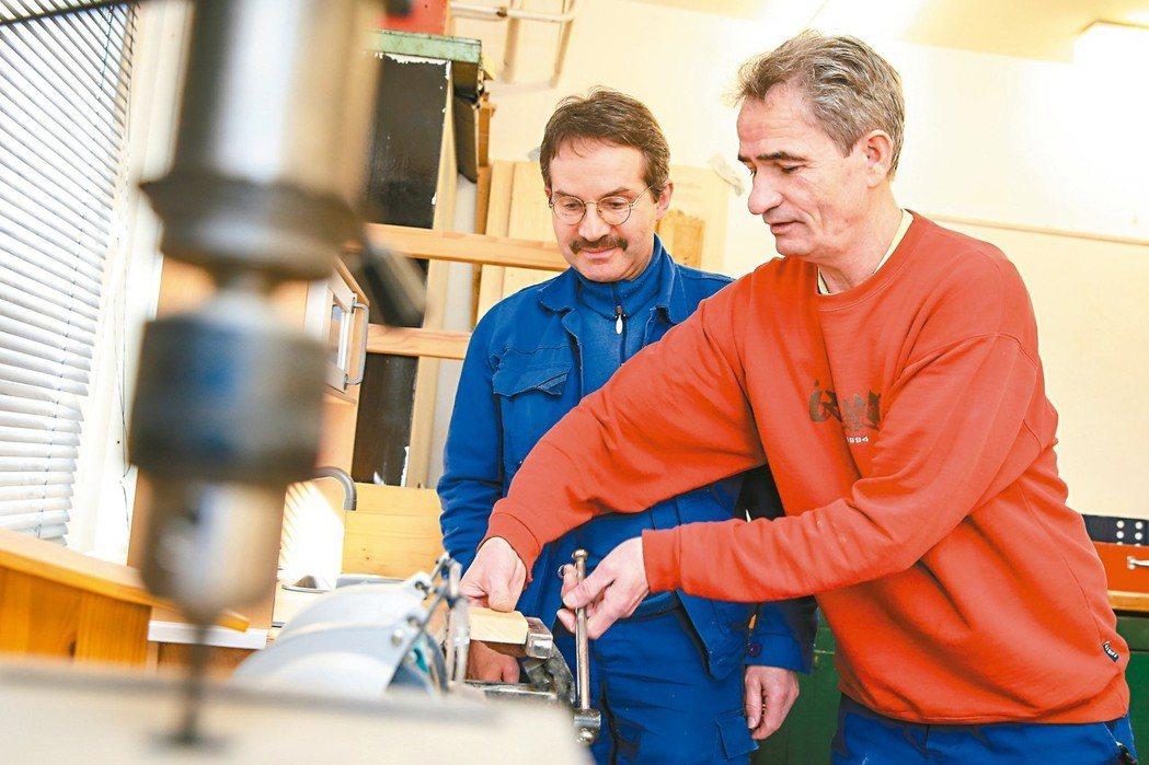 十二年培訓師哈同(右)在職訓中心輔導失業民眾學習木工技藝,幫助他們取得謀生技巧。...