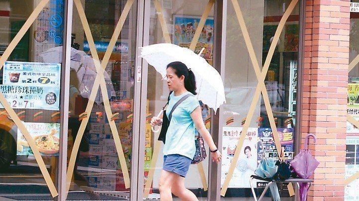 強颱瑪莉亞來勢洶洶,一家便利商店的玻璃貼滿膠帶,防範颱風來襲。 記者侯永全/攝影