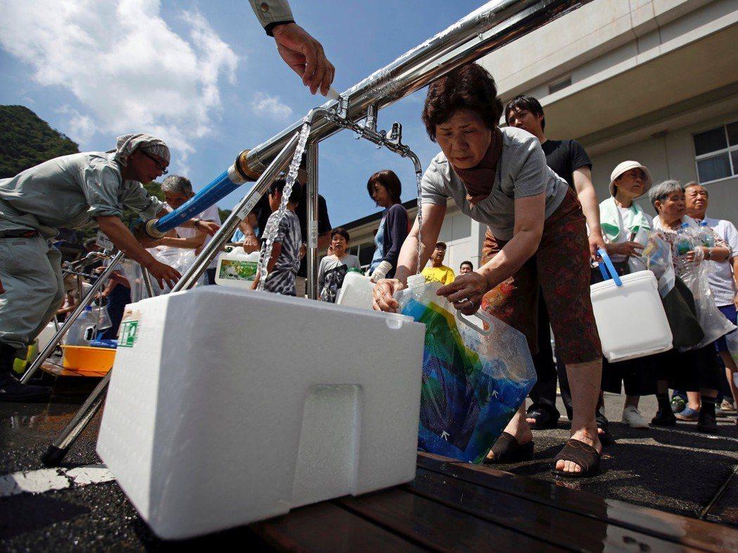 廣島縣三原市的避難民眾,正在取用緊急用水。 圖/路透社