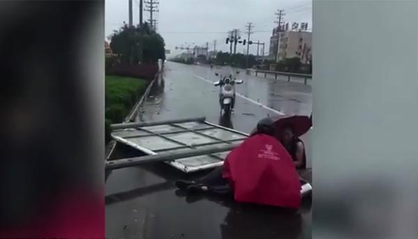 公路邊有一塊長方形的路牌倒在地上,路牌下方壓著一名身穿黑色褲子的男子。圖/澎湃新...