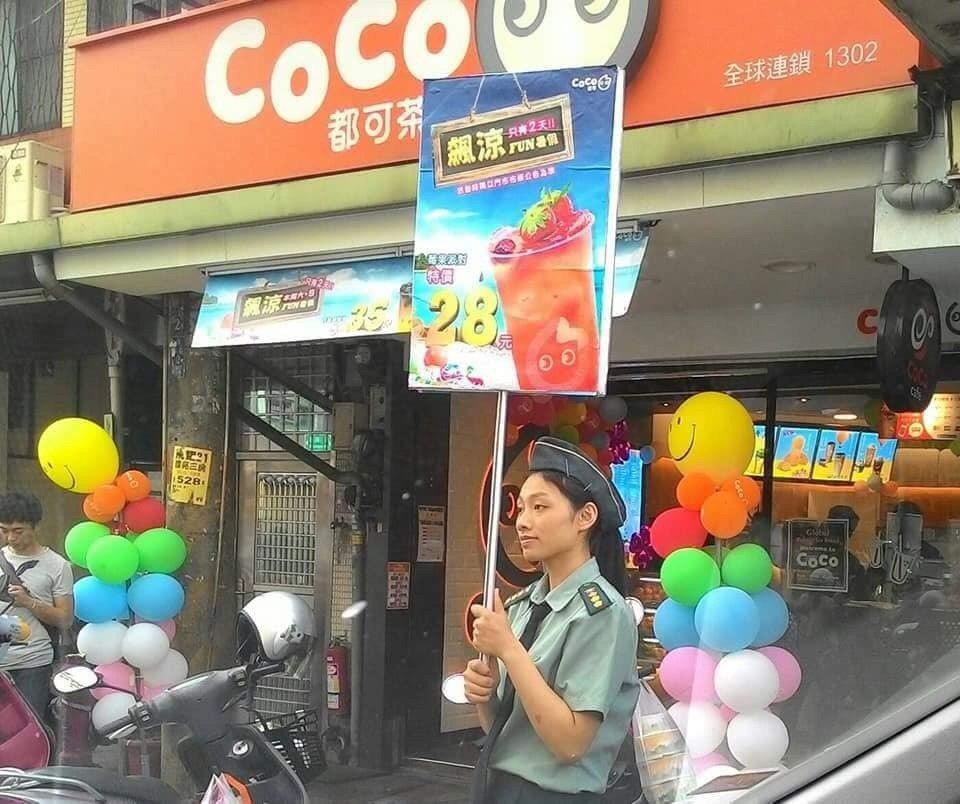 某知名手搖飲料連鎖店促銷飲品,店員穿上全套陸軍政戰上校女官服幟,扮成軍官舉牌在街...