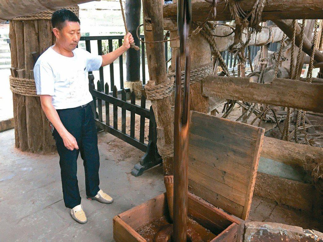 燊海井工作人員示範汲取鹵水。 記者汪莉絹、曾玉玲/攝影