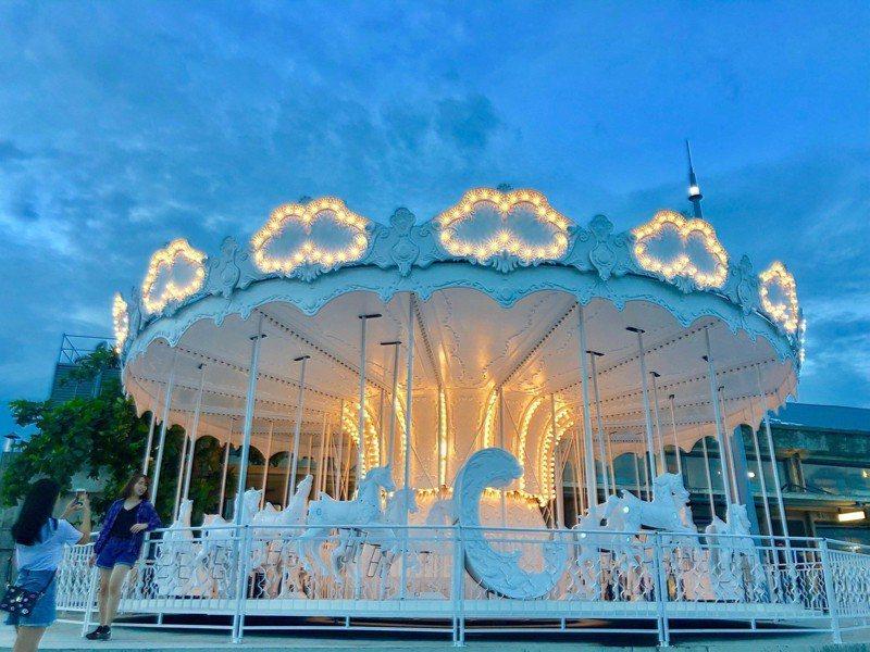 棧貳庫更用古典機械裝置藝術手法詮釋「夢想港濱」,打造純白旋轉木馬,已成打卡亮點。圖/高雄港區土地開發公司提供