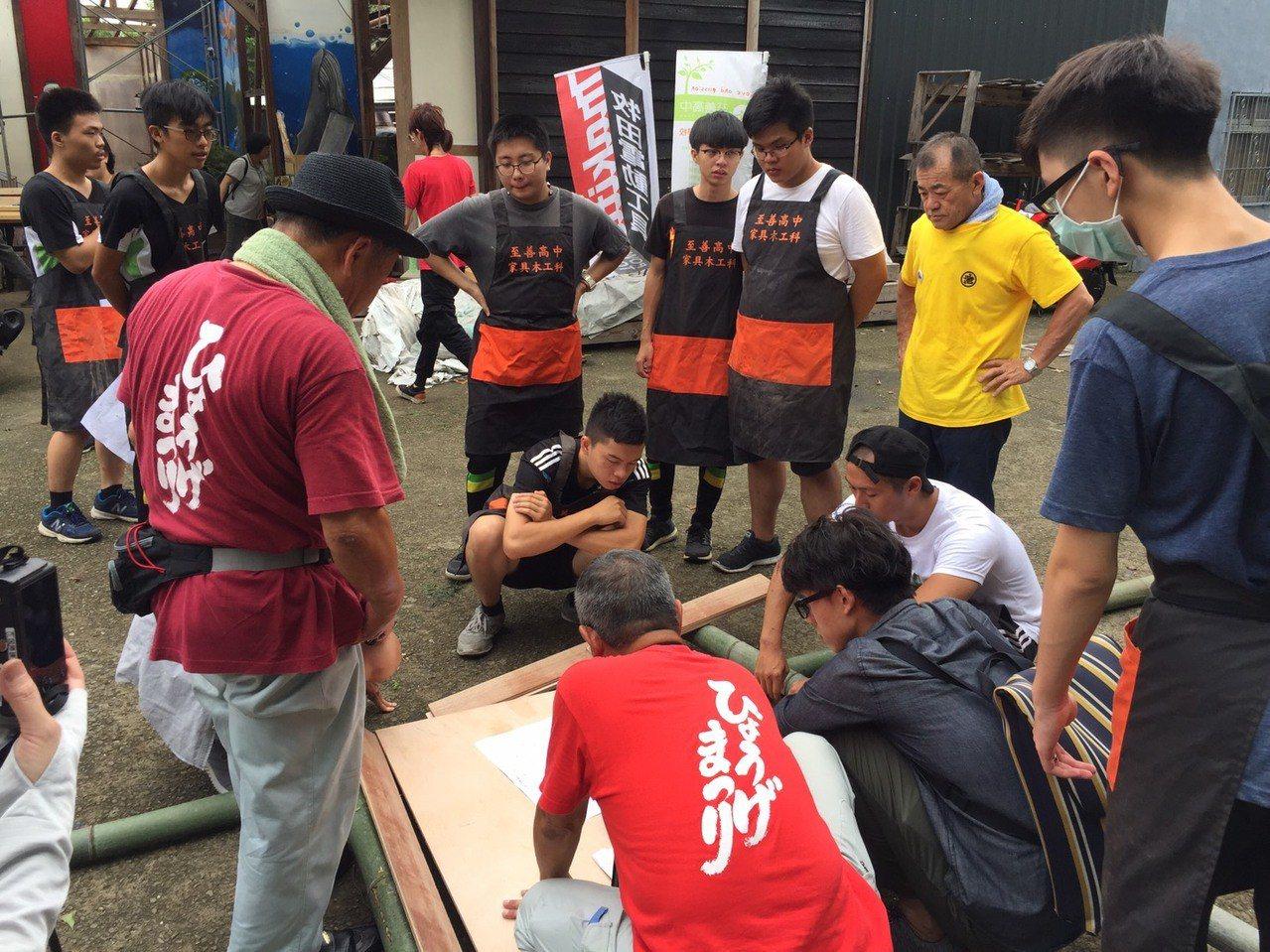 日本木工職人和至善高中家具木工科老師討論製作神轎細節,學生在一旁認真聽。記者鄭國...