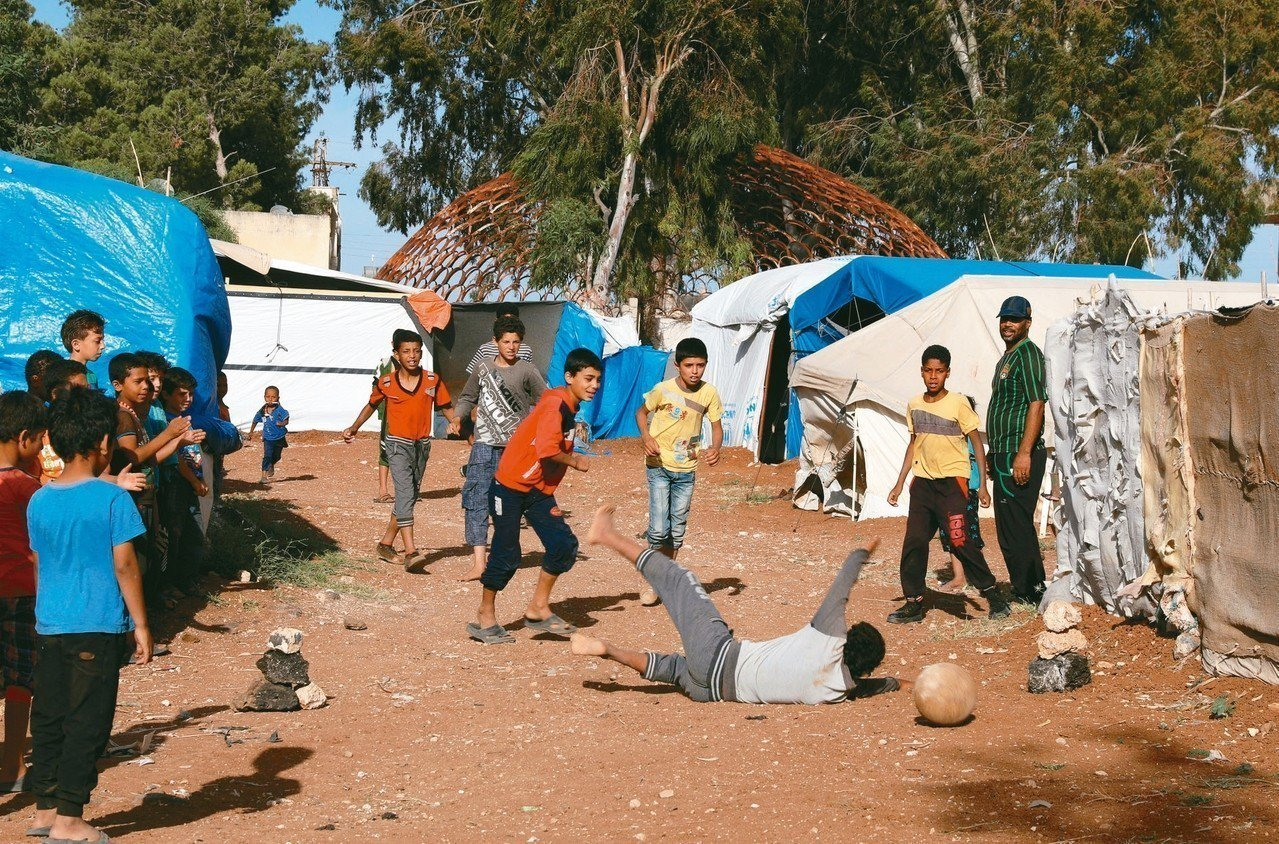敘利亞境內也有許多被迫離開家鄉的難民,在德拉的一處難民營中,兒童踢著足球。 (路...