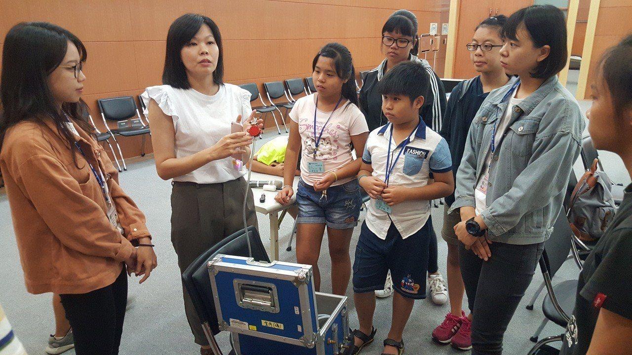 國衛院為青少年學生辦的「知識之旅」國中第一梯次昨天登場,學員聽取空氣測量採樣儀器...