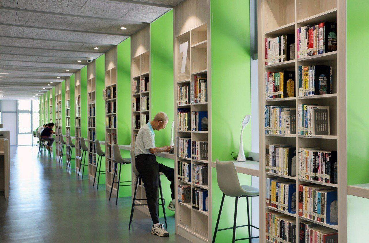 窗邊閱讀區亮綠色的書櫃壁面,與窗外景色相呼應,整個讀書環境充滿清新綠意。圖/新北...