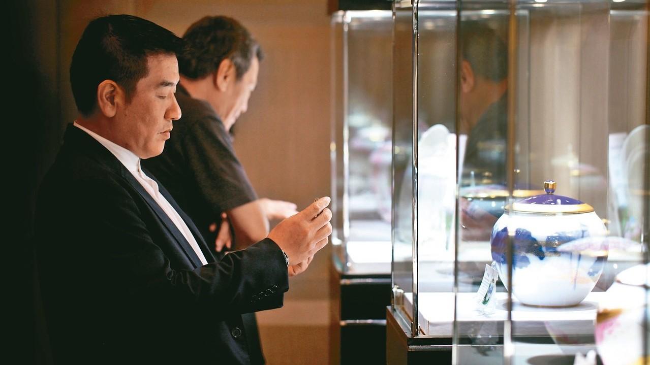 龍巖昨舉辦「桃花源」新商品鑑賞會,民眾仔細觀賞瓷器藝術。 龍巖/提供