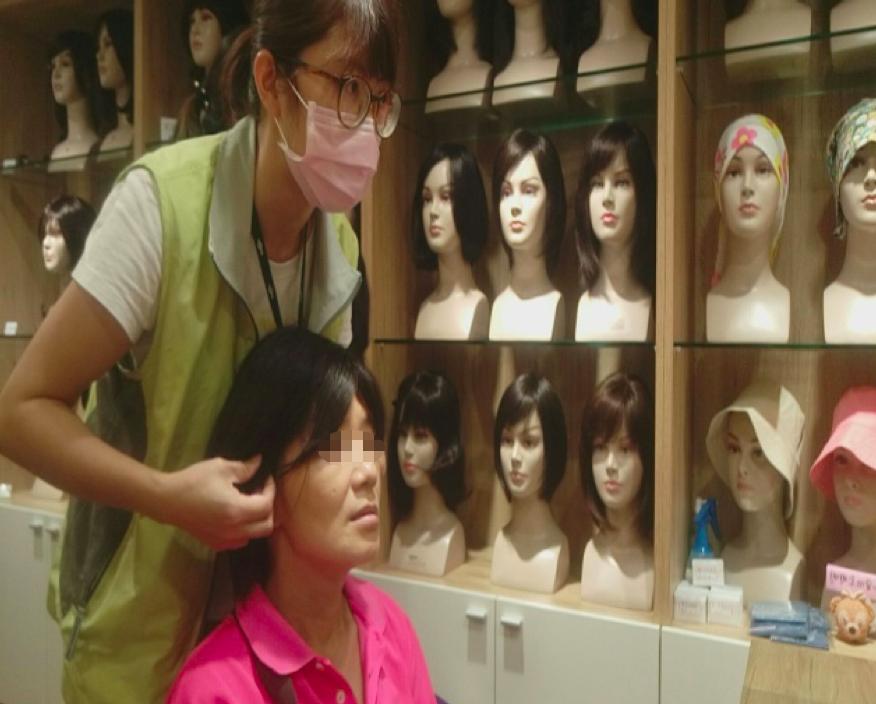 美髮師為呂女士設計整理假髮,戴上假髮的呂女士露出開心笑容。圖/榮總提供