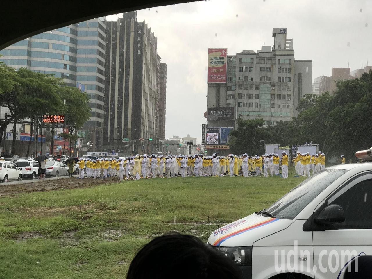 平實營區下起大雨,聽音樂會的民眾紛紛躲雨,法輪功仍留在原地。記者鄭維真/攝影
