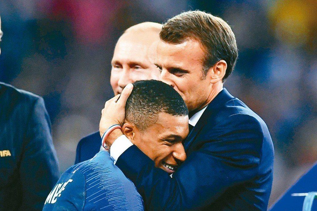 姆巴佩獲頒最佳新人獎時,與法國總統馬克宏相擁慶祝。 路透