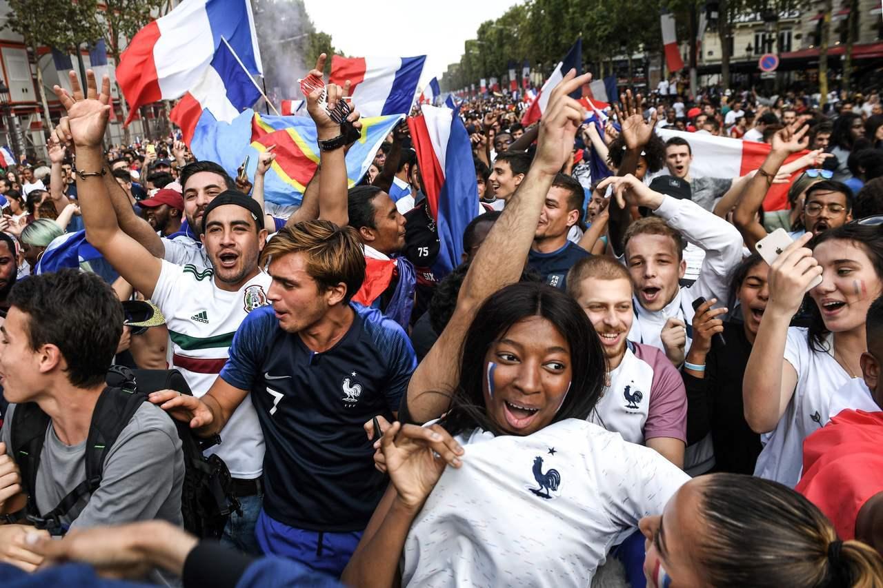 法國睽違20年再度奪下世足金盃,巴黎香榭麗舍大道湧入數十萬球迷,揮舞國旗、高聲歡...