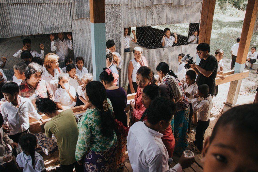 開幕典禮後學生與村民飲用乾淨過濾的水。 圖/實踐大學提供