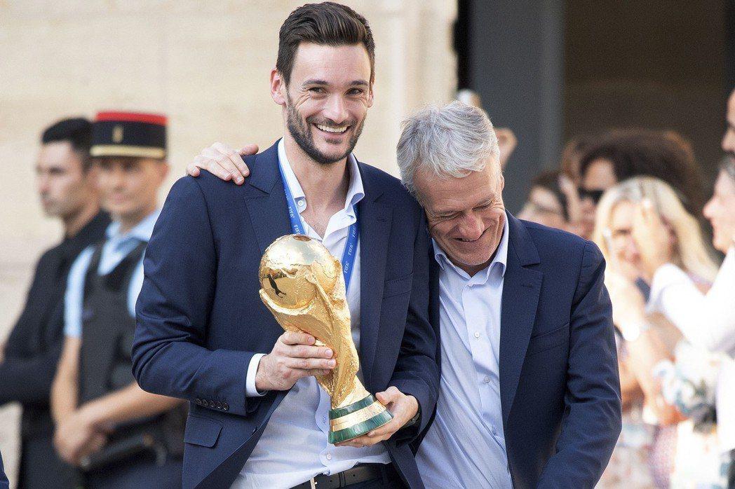 法國總教練德尚(右)摟著手拿世足賽冠軍盃的子弟兵洛里斯,參加法國總統馬克宏舉辦的...