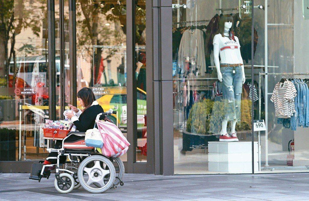 百貨公司櫥窗前,一位販售愛心商品的殘障人士,利用中午人潮空檔吃午餐,等著推銷商品...