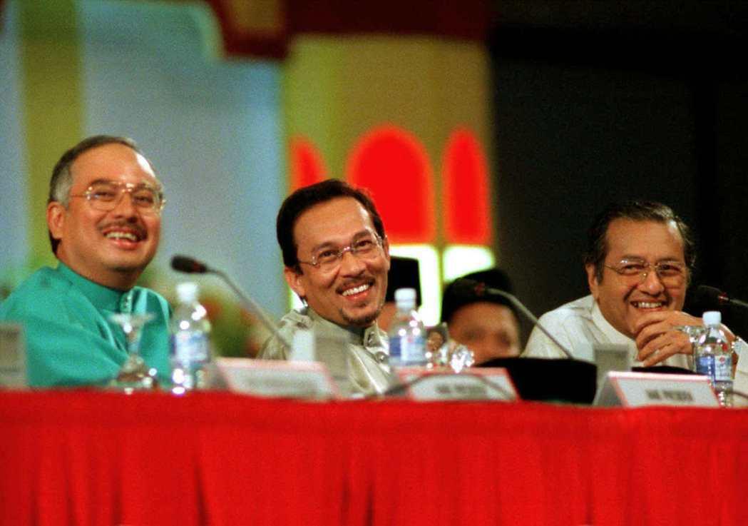 1998年,左起時任教育部長的納吉、副首相安華、首相馬哈迪出席巫統大會時相鄰而坐...