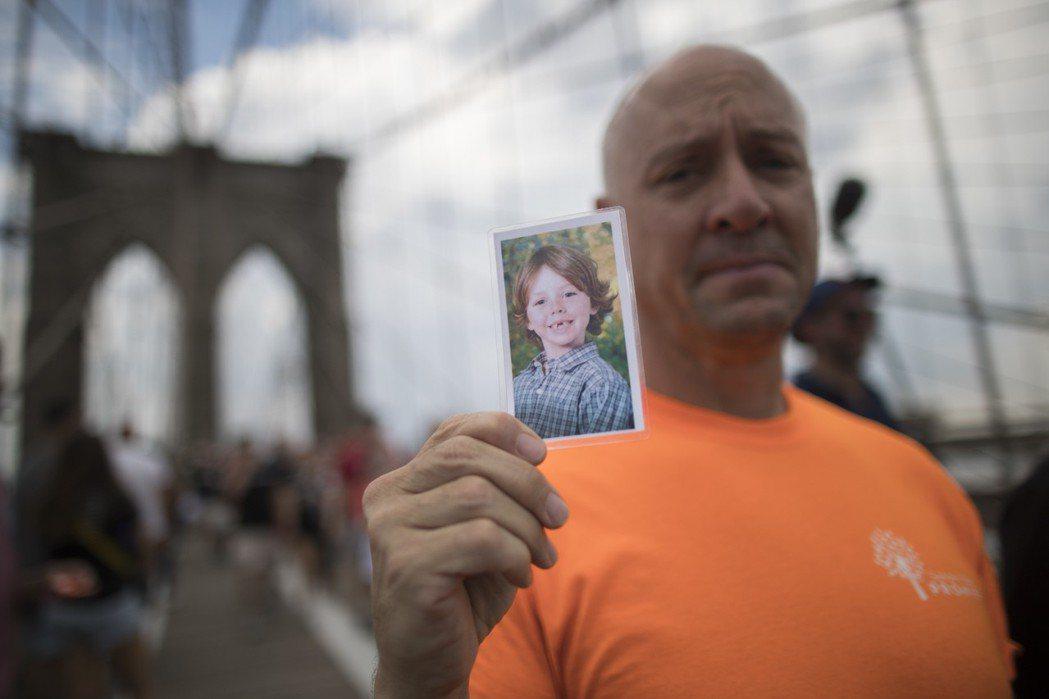 今年6月,聲援者手上拿著Sandy Hook校園槍擊案犧牲者的祈福卡,聲援反槍支...