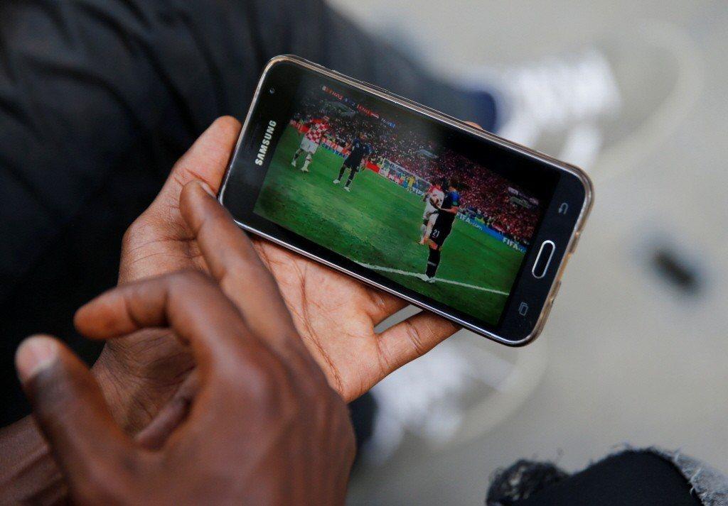 一名球迷以手機收看世界盃。 圖/路透社