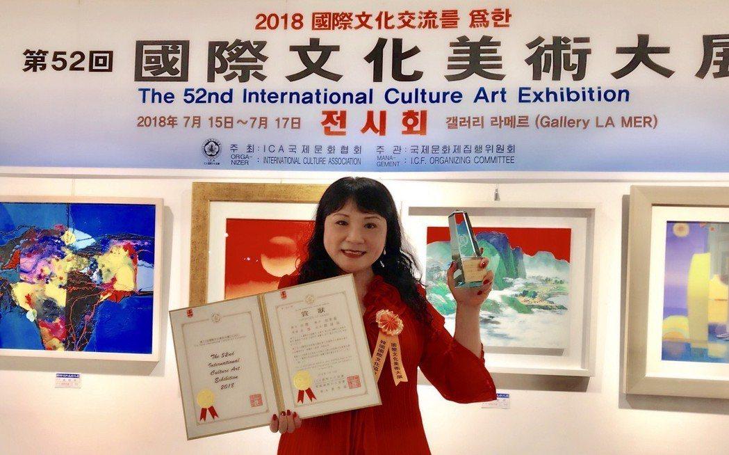 蔡淑珠在韓國獲得金獎後,高興拿著證書及金獎獎座在展出主場留下紀念。鄭芝珊/攝影