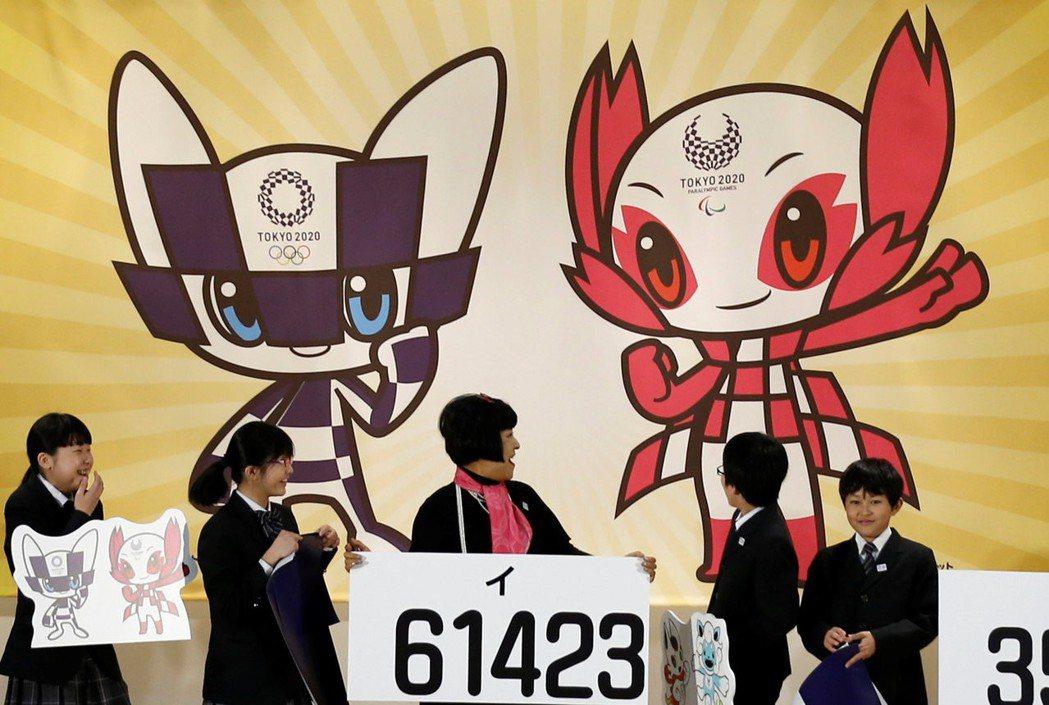 日本東京奧運吉祥物「未來永遠」(ミライトワ Miraitowa,背景圖左)。 路...