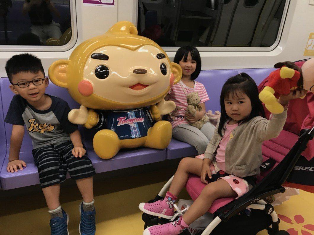 桃園機場捷運迎接暑假,以桃園吉祥物「ㄚ桃」、「園哥」設計專屬彩繪列車,塗了車廂內...