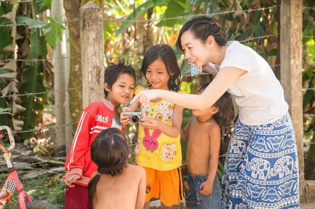 小維正在指導柬埔寨的兒童如何操作相機。圖/張維提供