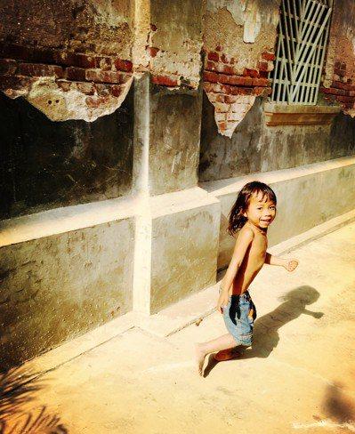 柬埔寨的孩子街道上帶著燦爛笑靨,一回頭就被相機捕捉下來。圖/張維提供