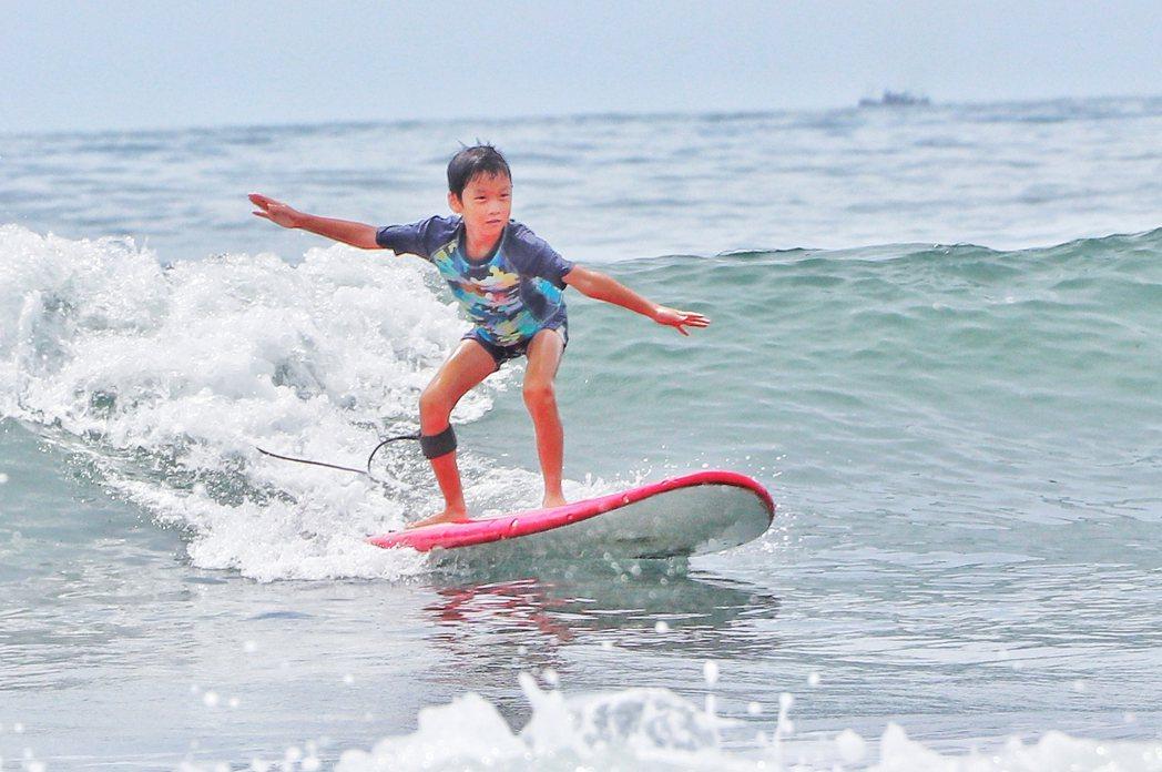 何豪傑站在海中捕捉小兒子衝浪身影。圖/民視提供