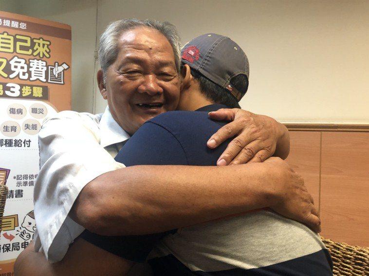 經營麵包店的吳永昌(左)經么子吳俊俞捐肝後重拾健康,他緊緊擁抱兒子,感謝兒子將他...