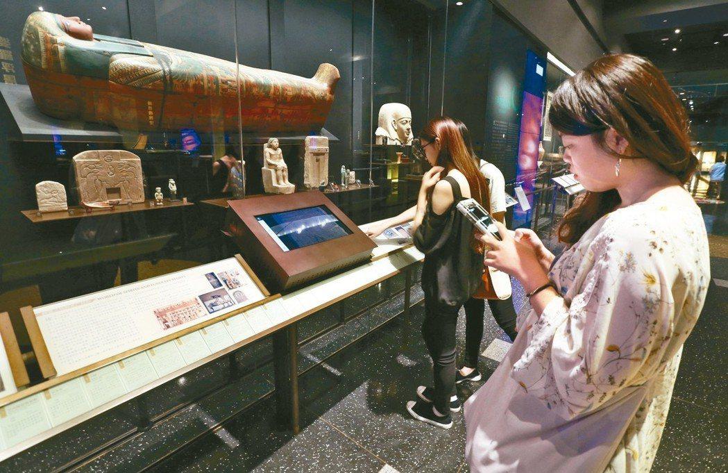 民眾手持手機內的AI機器人,參觀世界宗教博物館文物。 圖/聯合報系資料照片