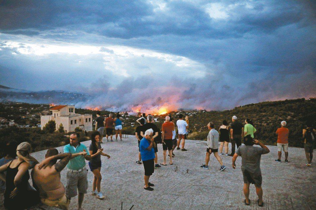 希臘首都雅典附近的拉斐那(Rafina)23日發生森林野火,許多民眾在遠處觀望。...