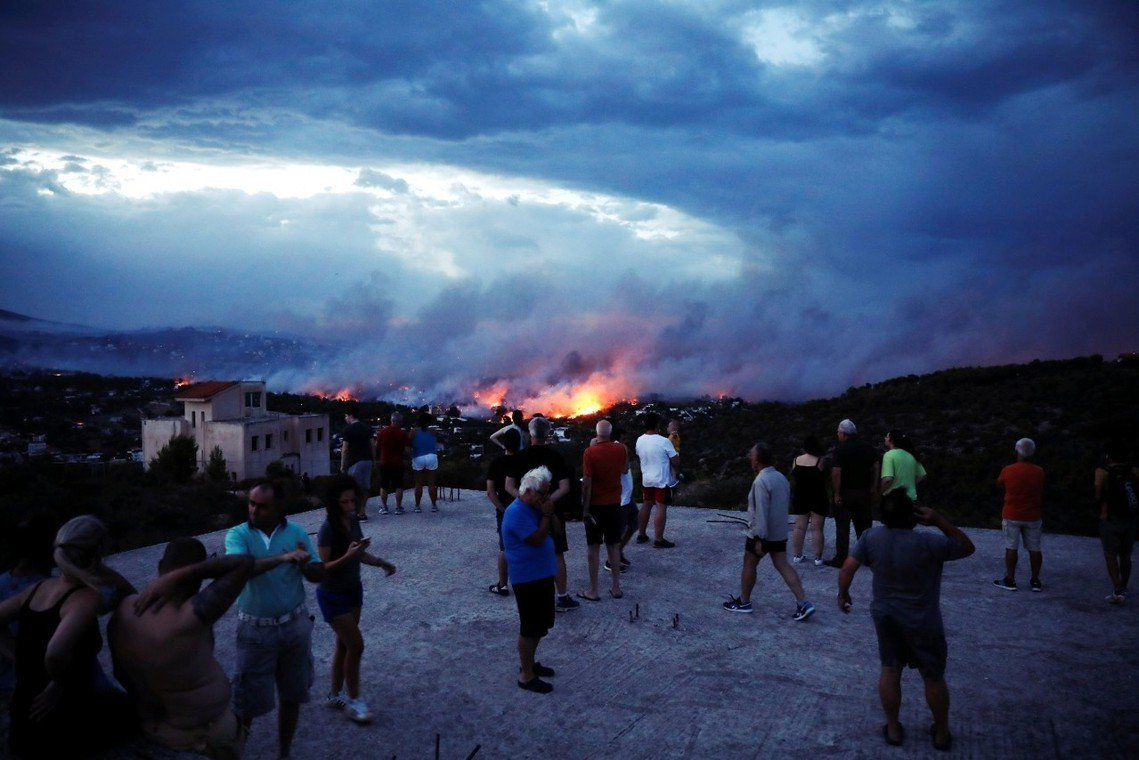 從雅典丘陵遠眺拉芬娜與馬蒂村的沖天烈焰。 圖/路透社