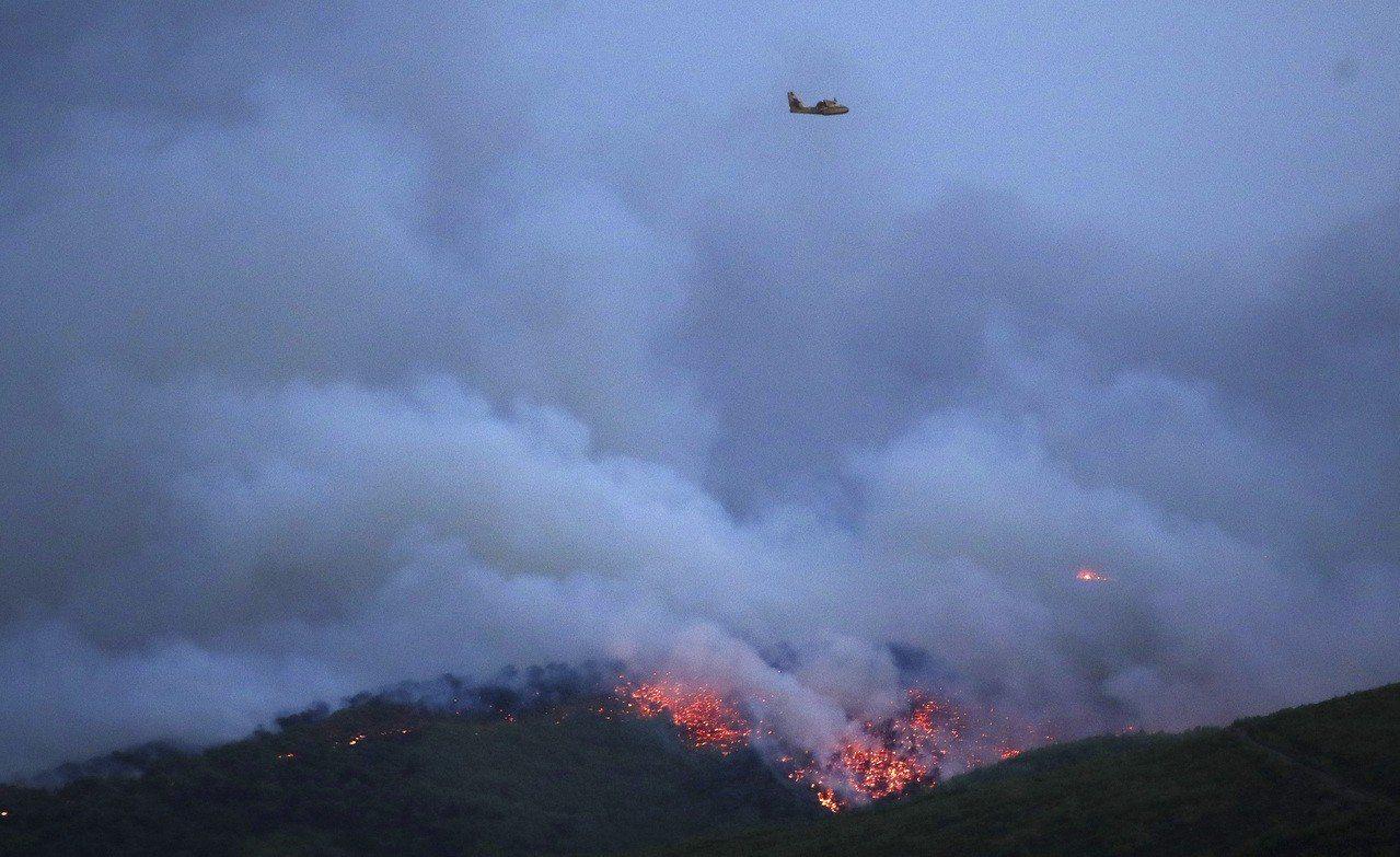 雅典郊區23日發生森林大火,雅典東郊馬蒂鎮上空有一架直升機在濃濃黑煙中救援。美聯...